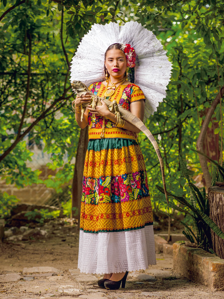 In Oaxaca the rich colours of textiles stem from long-held creative traditions. Miroslava Cruz Ferra wears heirloom attire and a white resplandor specific to southern Oaxaca. Photographed at a lizard conservation centre there, she holds an iguana, a symbol of the local people. Photo by Diego Huerta.