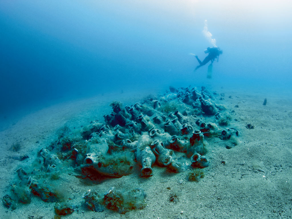 Off the Albanian coast, a diver examines amphorae, cargo from a Roman-era shipwreck. Photo by Elaine Ferritto Calip.
