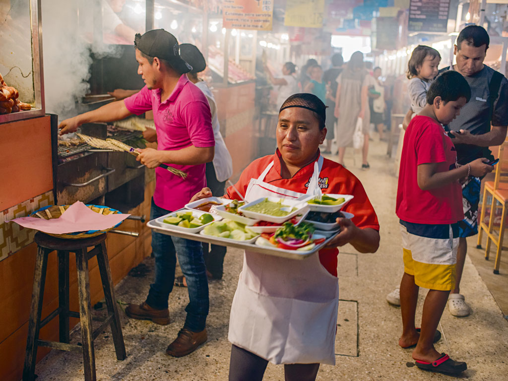 As in Oaxaca City's other markets, 20 de Noviembre market brims with food stalls serving everything from chicken soup to hot cocoa. Locals head to this part of the market for its tasajo, thinly sliced grilled beef, accompanied by grilled vegetables and a tlayuda tortilla. Photo by Adam Wiseman.