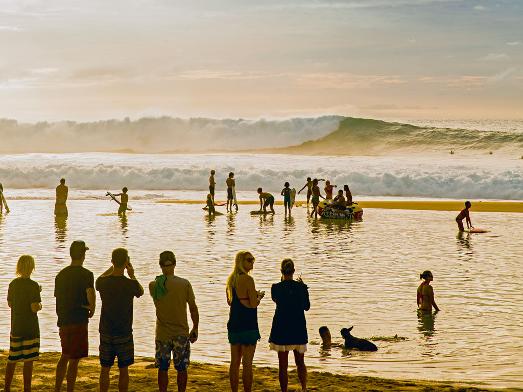 "Surfers of all ages gather at sunset on the North Shore, which hosts some of the world's most prestigious annual big-wave competitions, including the Quiksilver invitational (known as the ""Eddie""). Photo by Erin Kunkel."