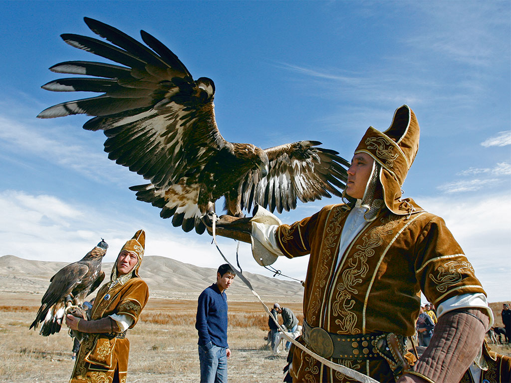 A Kirghiz hunter releases an eagle during Salburun, a hunting festival where participants compete in falconry and archery. Photo by Vladimir Pirogov/Shutterstock.Com/Shutterstock.