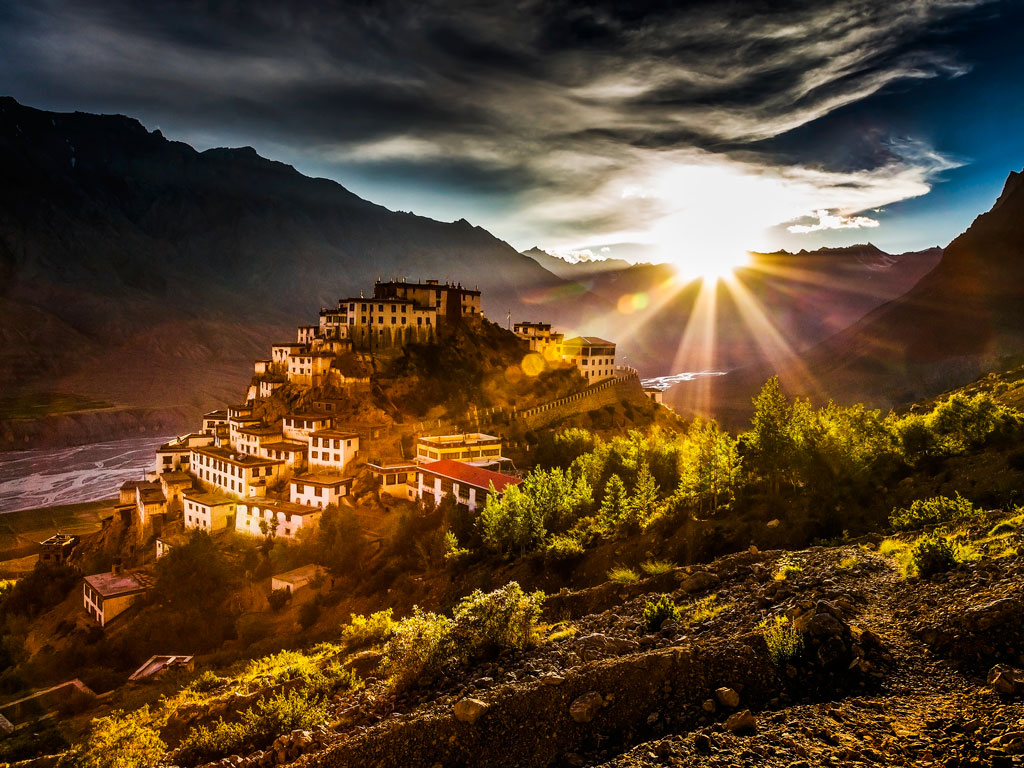 The summer sun shines over Spiti's Key Gompa, bathing the mountain valley in a golden hue.