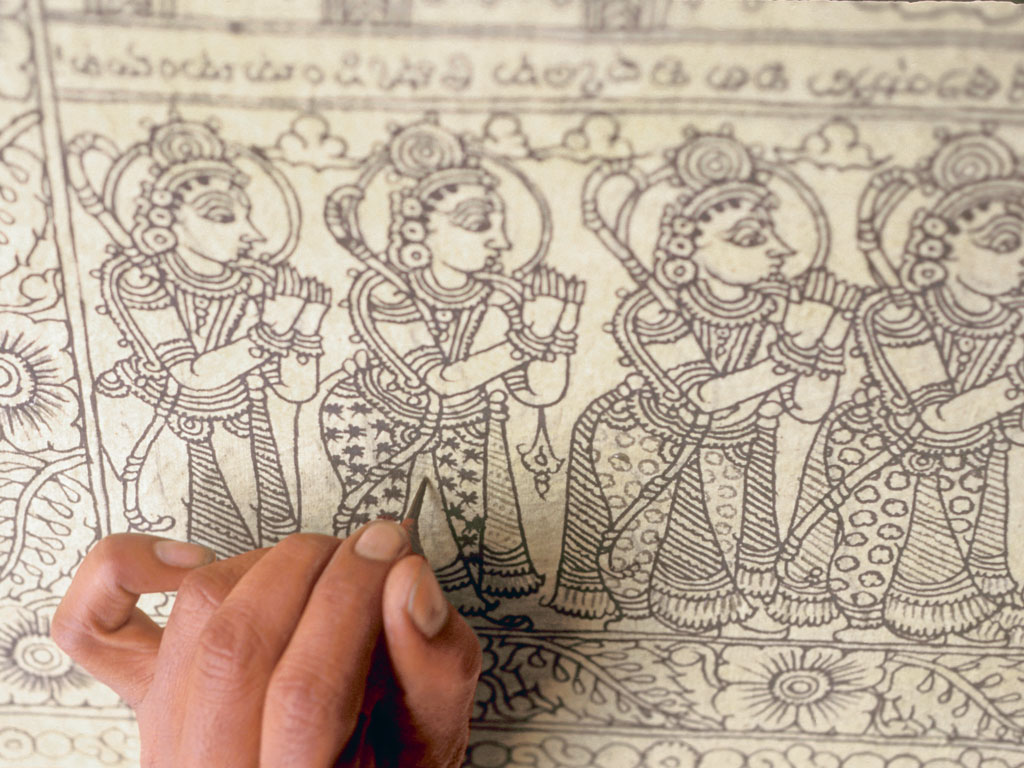 A kalamkari artist dexterously works his fingers through the intricate details on a textile patch. Photo by IndiaPictures/Contributor/Getty Images.