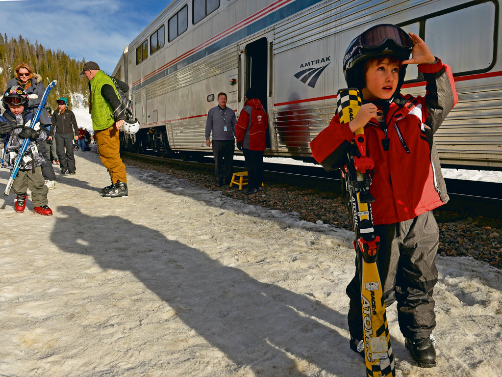 Bundled in layers, a group of kids gets off an Amtrak train, all geared to unleash their skiing skills in Colorado's Winter Park area. Photo by: Helen H. Richardson/Contributor/Getty images