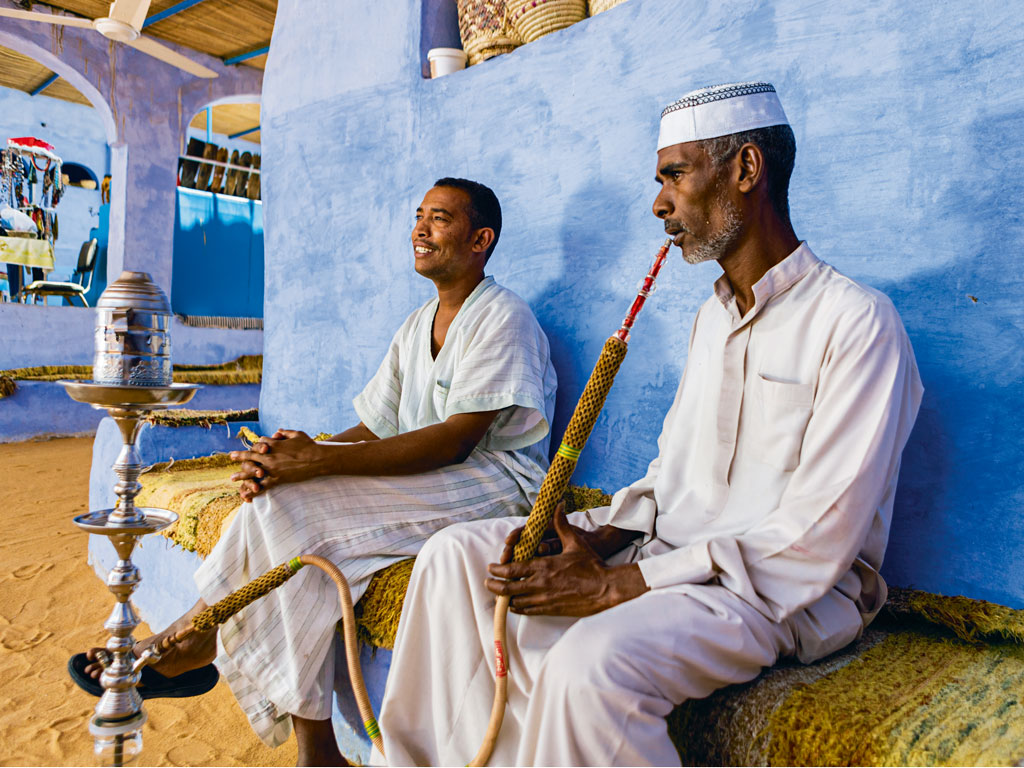 Evenings find locals smoking a shisha and drinking tea outside their homes in Aswan. Photo by: hadynyah/E+/Getty Images