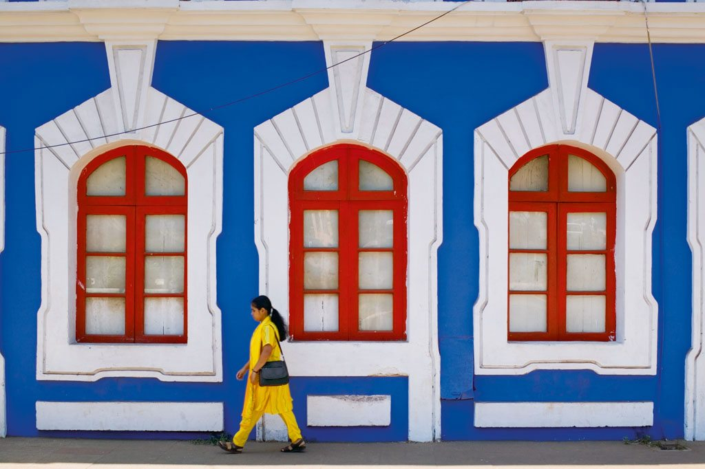 Woman Walking By Colorful House