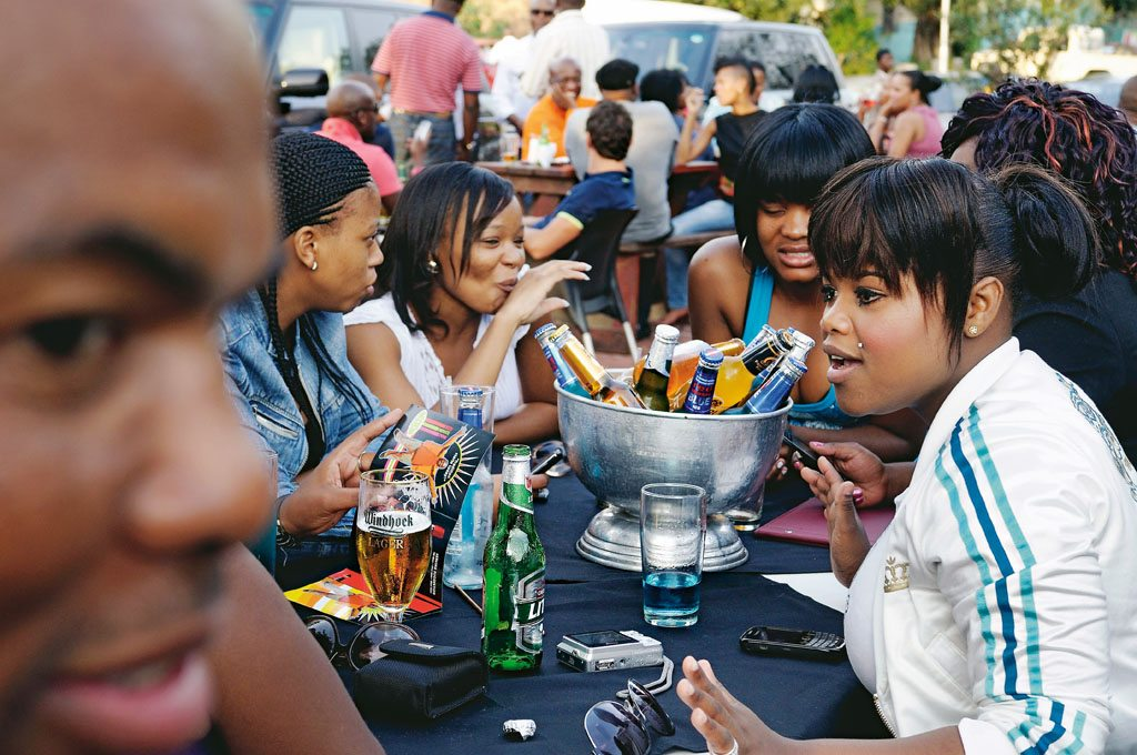 Friends in Soweto gather for drinks and soak up the outdoor vibe at Sakhumzi Restaurant on historic Vilakazi Street. Photo: Bram Lammers/Hollandse Hoogte/Redux