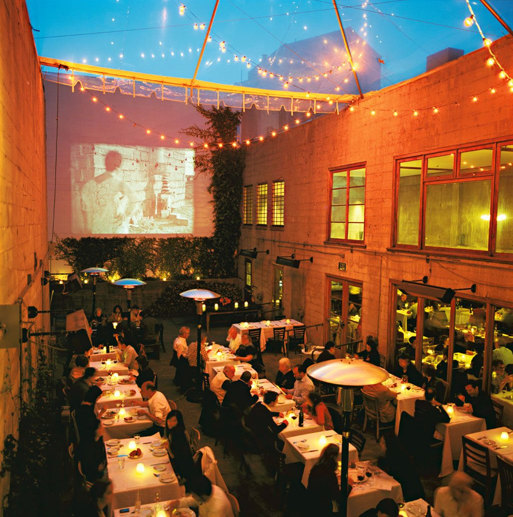 Patrons at the Foreign Cinema in San Francisco enjoy an alfresco candlelight dinner and a film projected on a wall. Photo: Susan Seubert