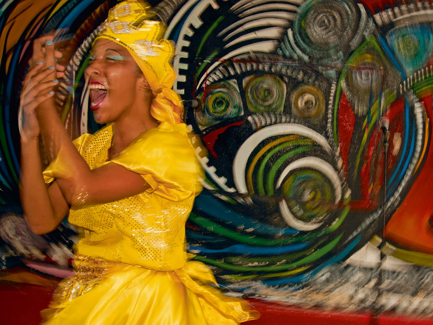 In Havana's Callejón de Hamel project known for its Afro-Cuban art, a young woman performs the ritualized dance of the orisha Ochún, the saint of sensual and flirtatious femininity. Ochún can always be identified by her yellow dress. Photo: Britt Basel