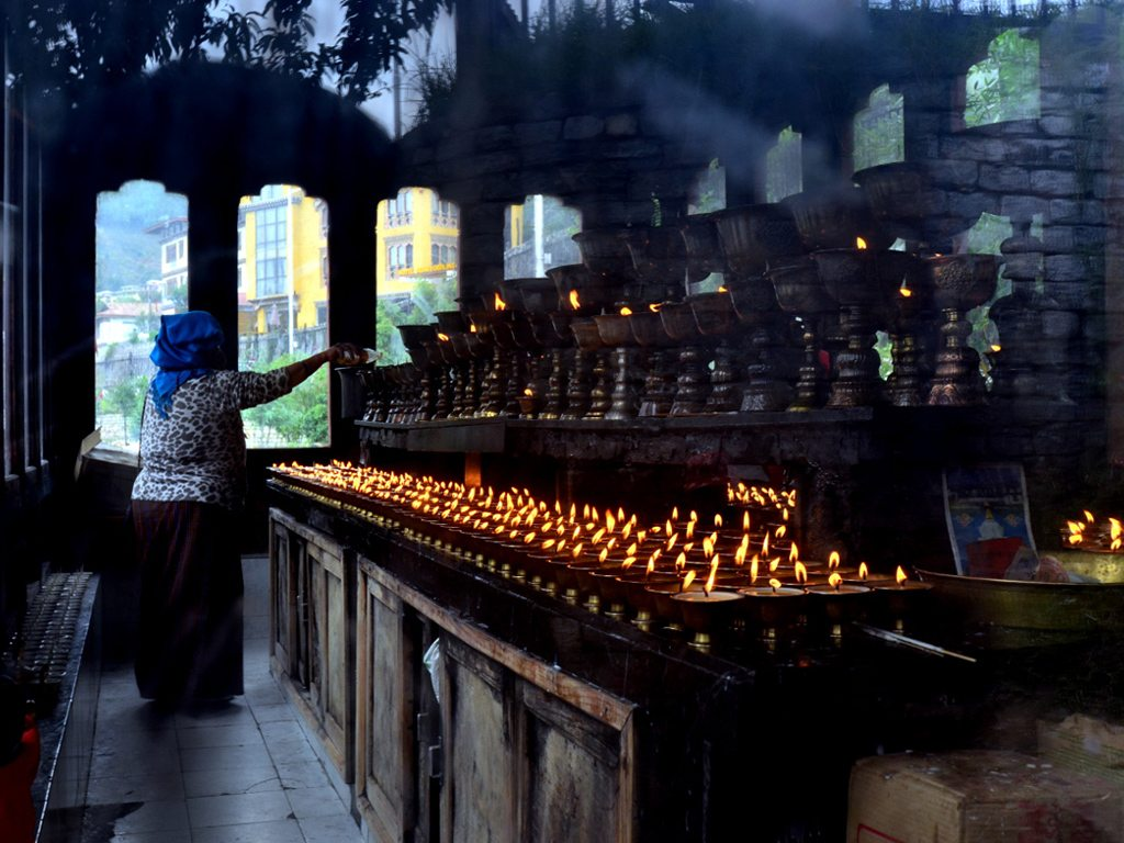 Prayers are carriers of hope, faith and new beginnings. Seen here is a devotee lighting a lamp as she offers her day's prayers at Thimpu's National Memorial Chorten.
