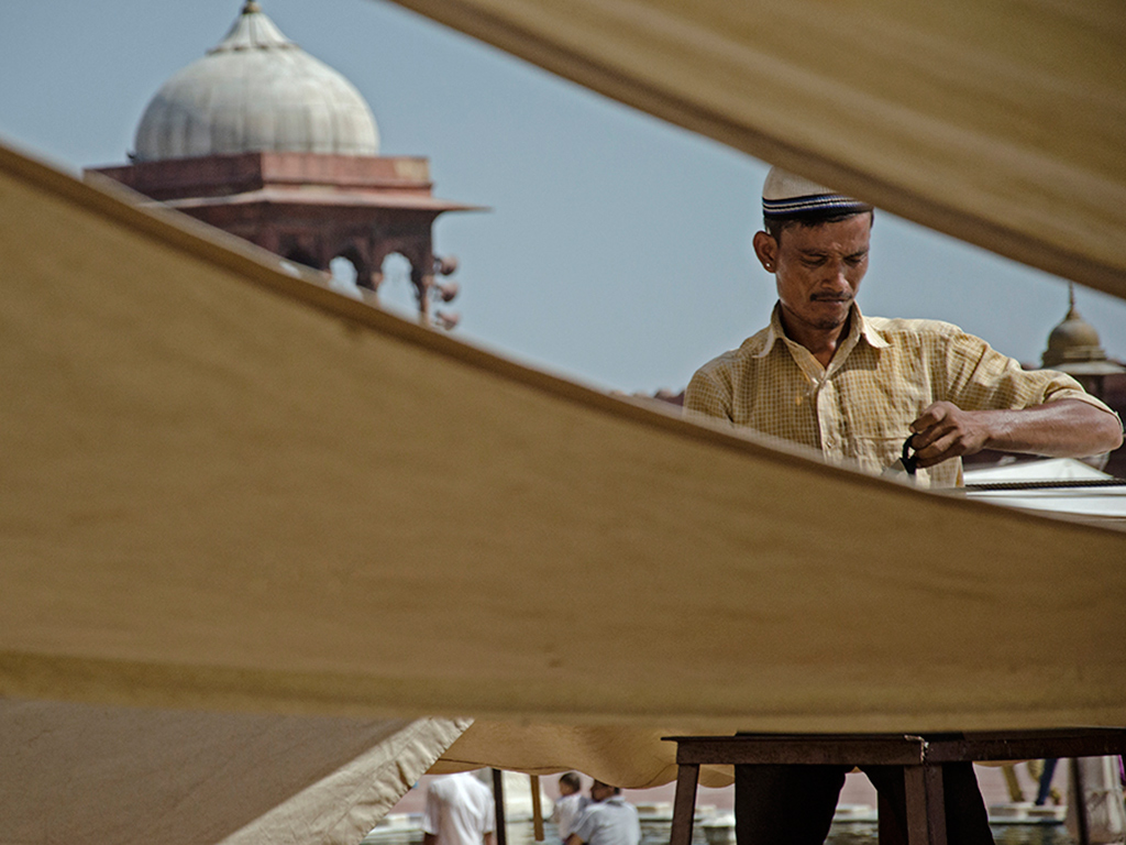A worker sets up tents and makes necessary arrangements before the morning prayers at Delhi's Jama Masjid.