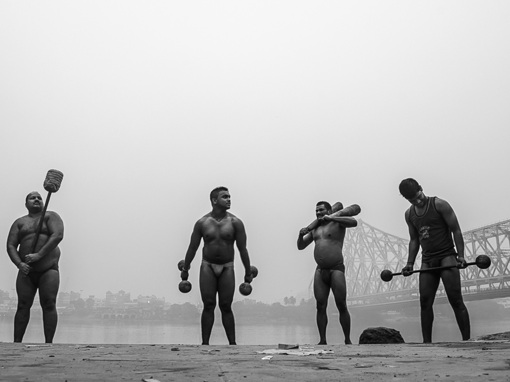 Pehelwans warm up along the banks of the Hooghly, in Kolkata, before beginning their morning exercises in a local akhara.