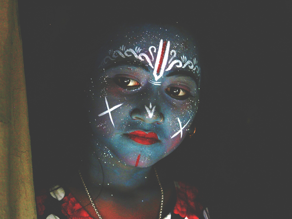 A young girl has her face painted as a god during the annual Gajan festival, that goes on for a month in West Bengal.