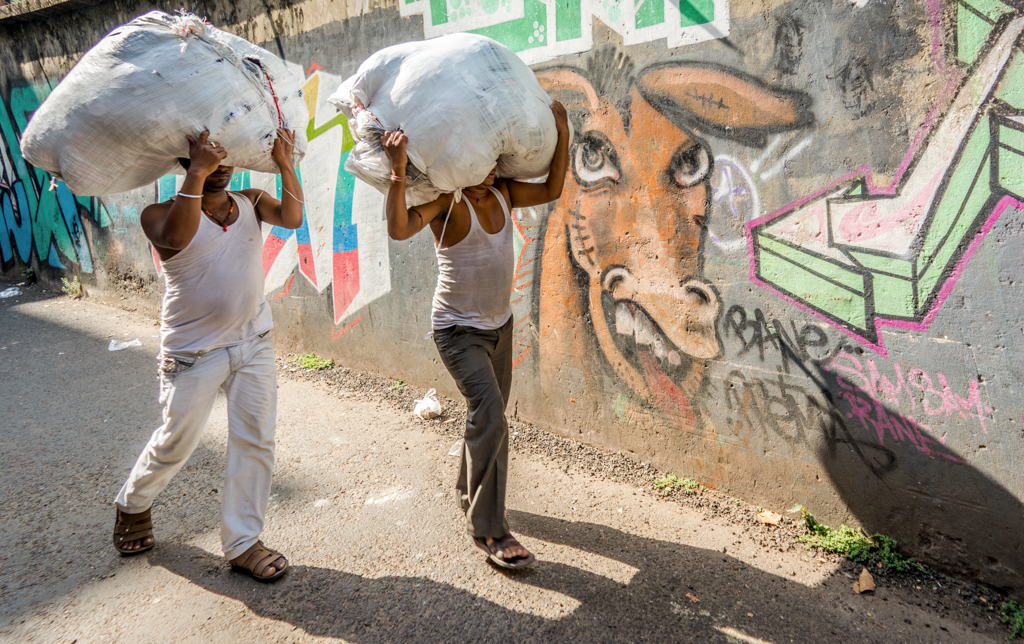 From the streets of Kolkata, a humorous juxtaposition of two men carrying load on their heads, with graffiti of a donkey laughing in the background.