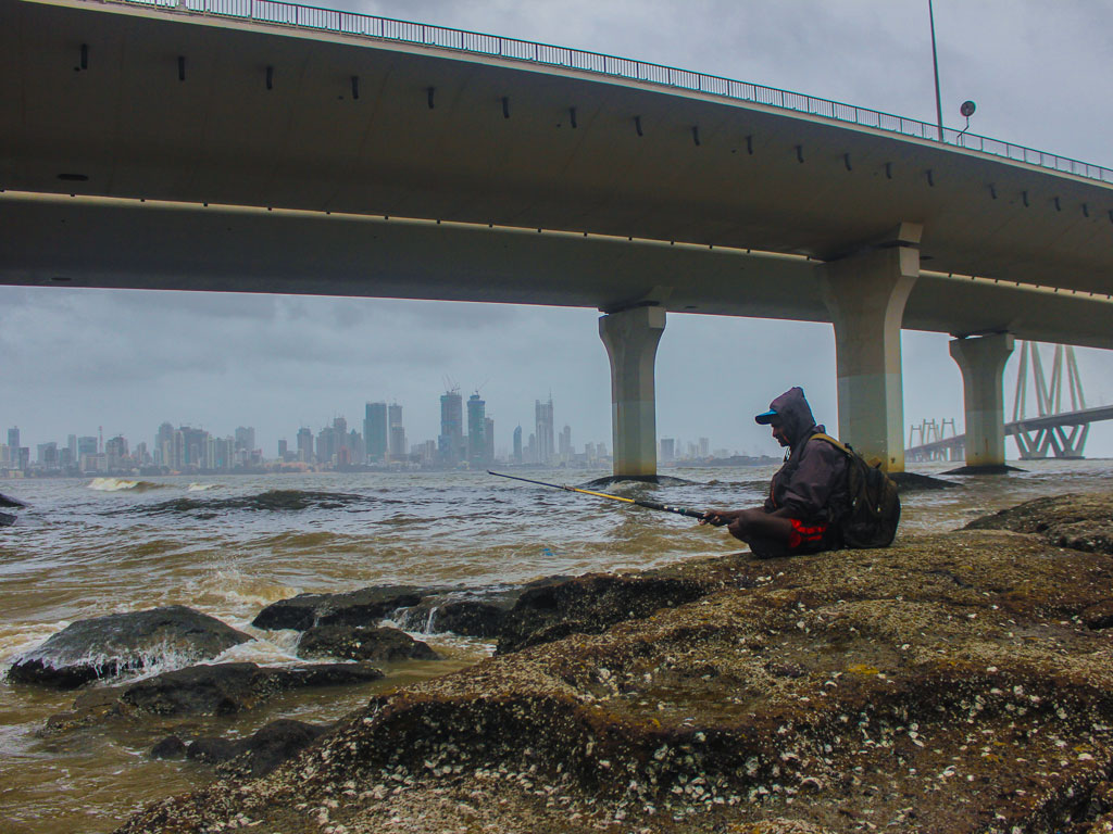 A little bit of rain is no reason why a man can't fish in peace, is it? Plus there's the Mumbai skyline to feast one's eyes on.