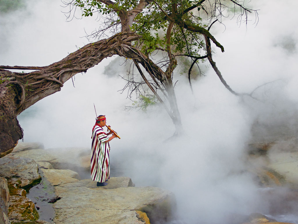 A shamam plays a traditional flute alongside Amazonian Peru's Boiling River. Photo by Sofĺa Ruzo.