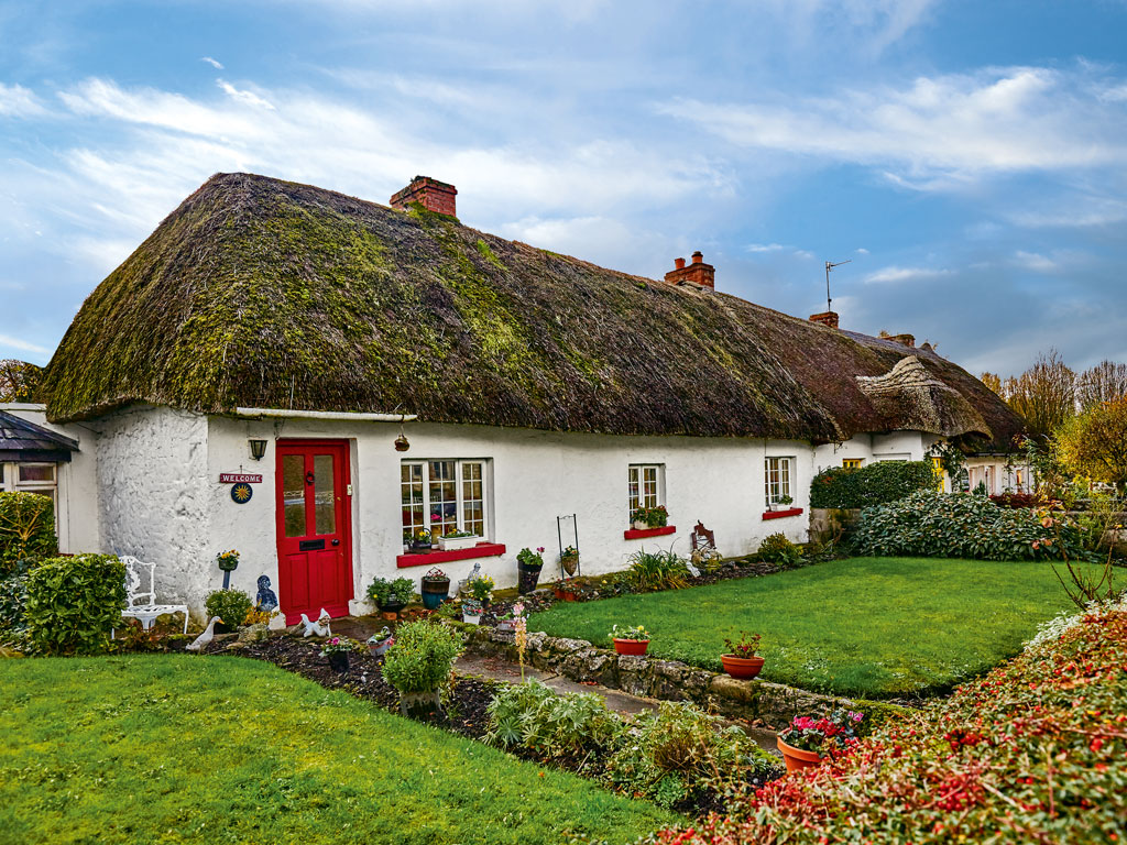 The thatched cottages in Adare were built int he 19th century for workers constructing Adare Manor. They now house restaurants and craft shops. Photo by: Peter Unger/Lonely Planet Images/Getty Images