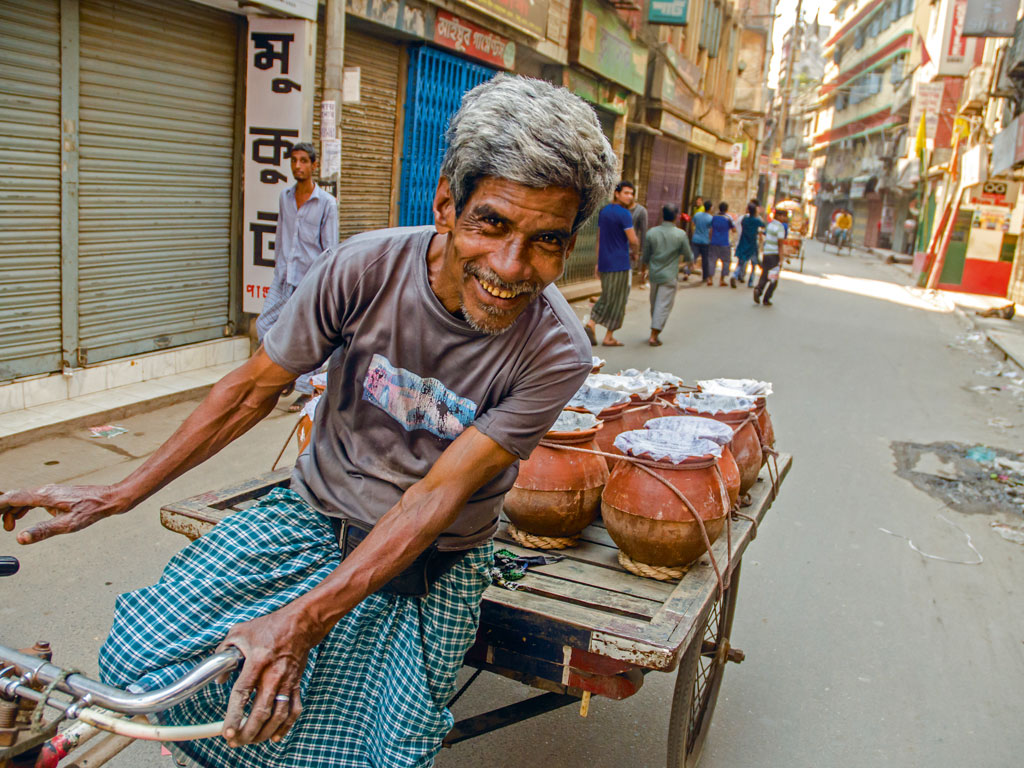 A vendor transports yoghurt to the restaurants on the empty streets of old Dhaka, happy to avoid weekday traffic on a Friday.