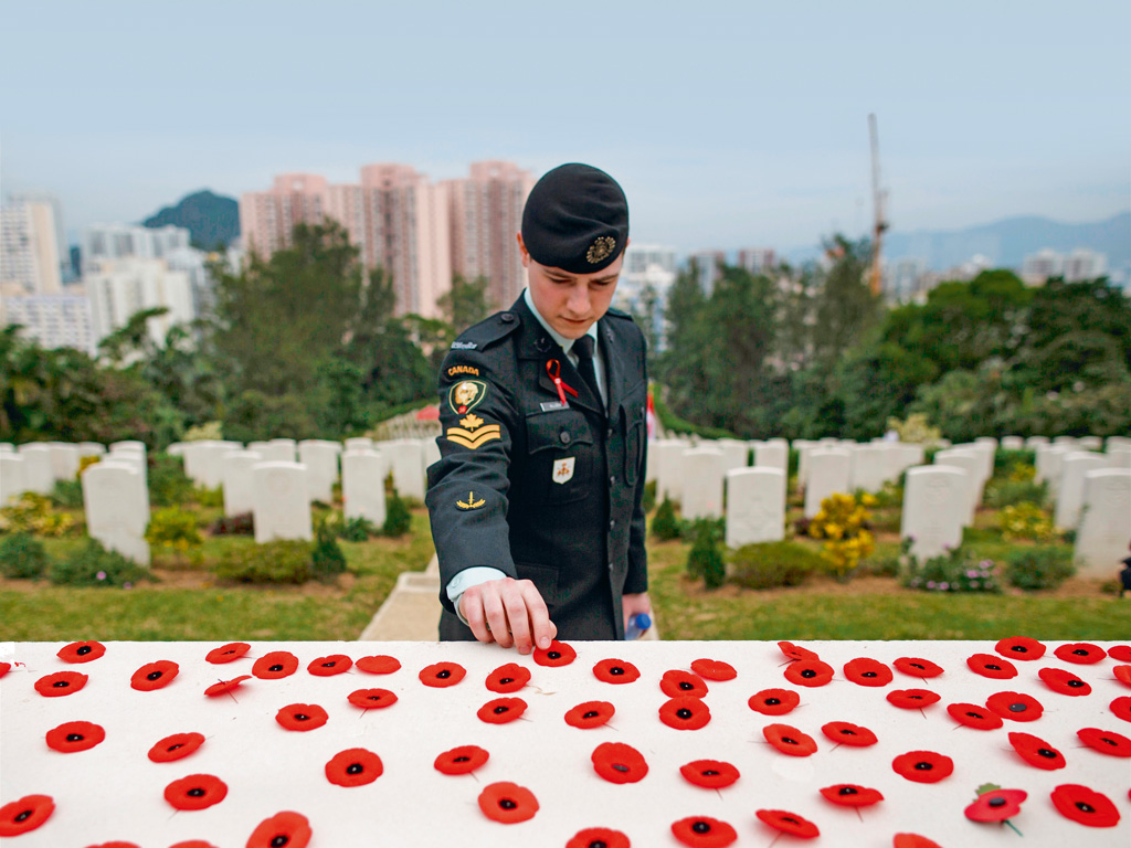 A member of the Canadian Armed Forces places a poppy over the Altar of Remembrance, in Hong Kong's Sai Wan War Cemetery, honouring those who died during World War II. Photo by: Tengku Bahar/staff/AFP/Getty Images