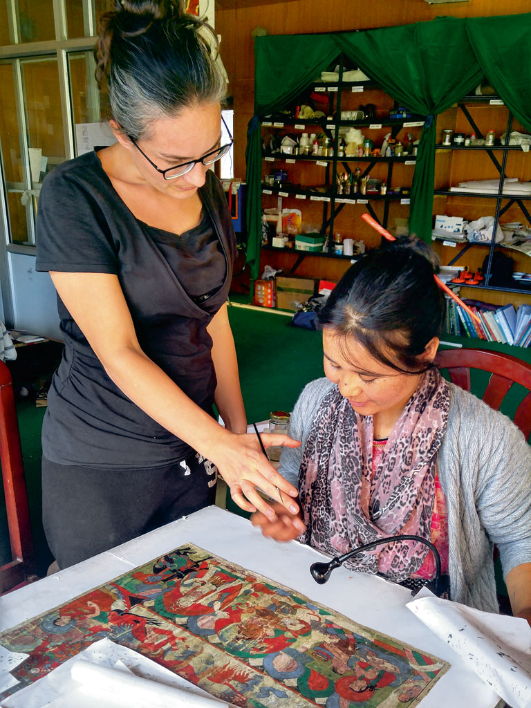 French restorer Nelly Rieuf trains locals to restore thangkas and other artefacts as part of the Matho Monastery Museum project. Photo by: Prachi Joshi