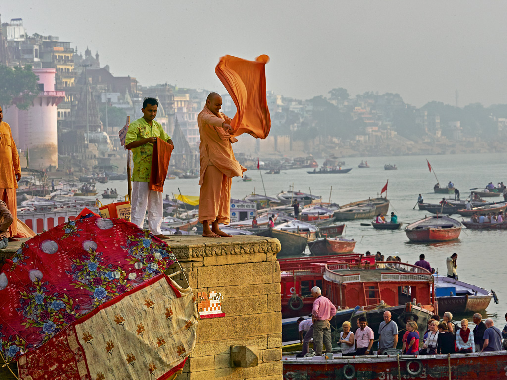 After a dip in the holy waters of Varanasi, pilgrims wash and dry their clothes by the ghats.