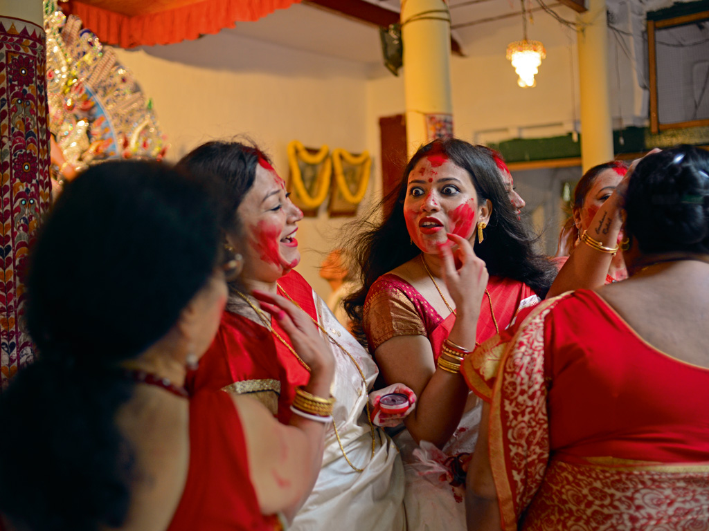 Seen as a manifestation of the daughter, Durga is sent off with wishes of marital bliss from married women. They smear sindur on the idol and each other in a ritual known as sindur khela. Photo by: Shraddha Bhargava