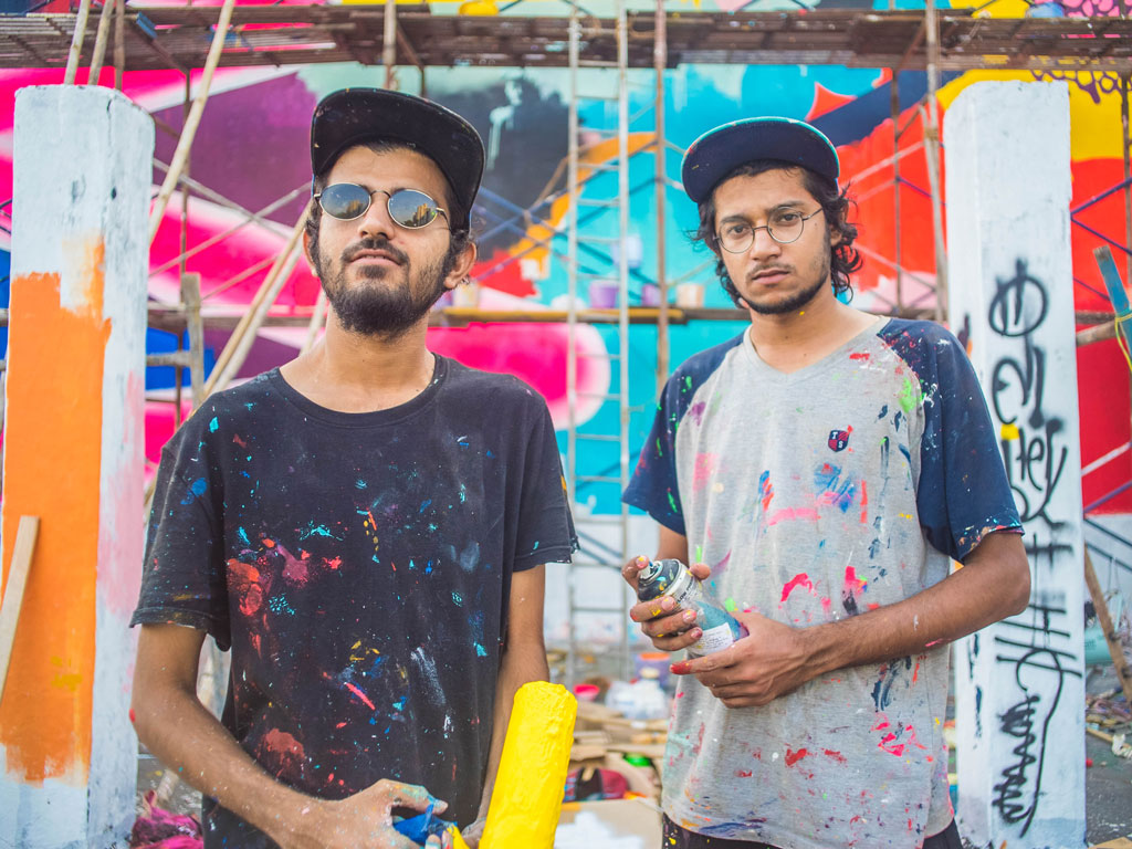 The street art duo, Do and Khatra, framed against 'Life at Sassoon', one of their installations at Sassoon Docks. Photo by Akshat Nauriyal.