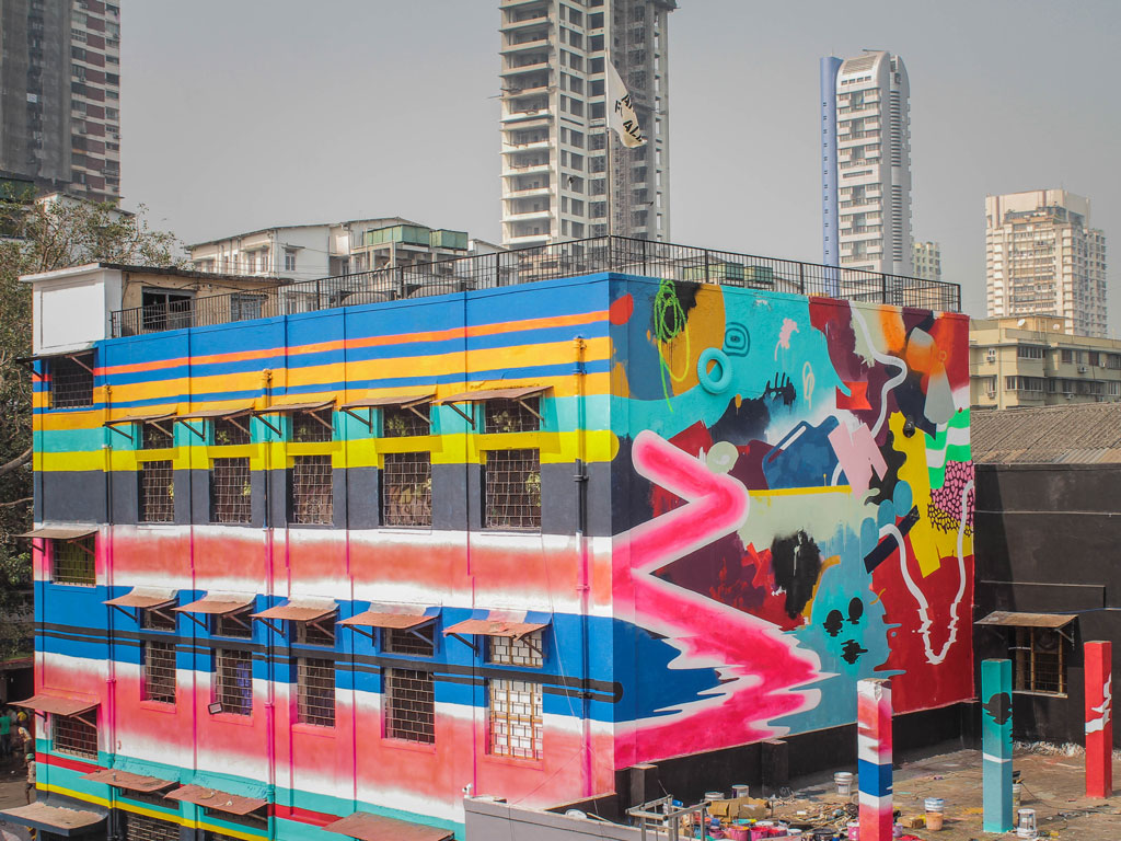 Do and Khatra, an artist duo from Gujarat, created a mural which is an abstraction of elements depicting the life and objects of Sassoon. If you look closely, you'll see the pink zigzag line is the road to Sassoon, and there might be a barber or two in the shadows. To add specificities to the mural on the façade, three dimensional objects found at the site like tyres and cans make up the composition of the artwork. Photo by: Pranav Gohil