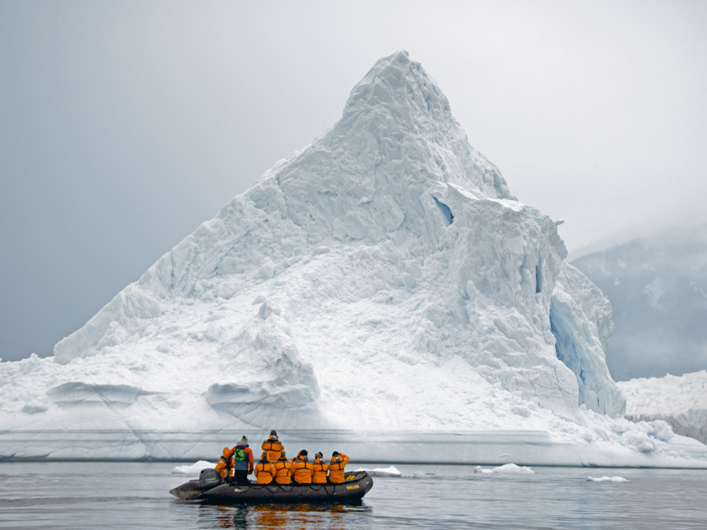 In the starkness of Antarctica, a Zodiac raft stops in awe and passengers in their yellow jackets realise their scale against the breathing, blue ice. Photo by Himali Singh Soin.
